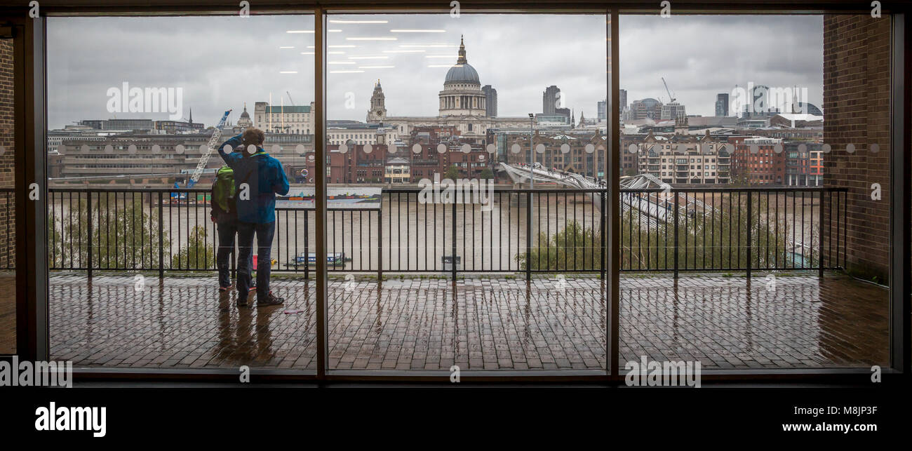A couple study a schematic and take in the view from Tate Modern across the Thames showing Foster's Millennium - Stock Image