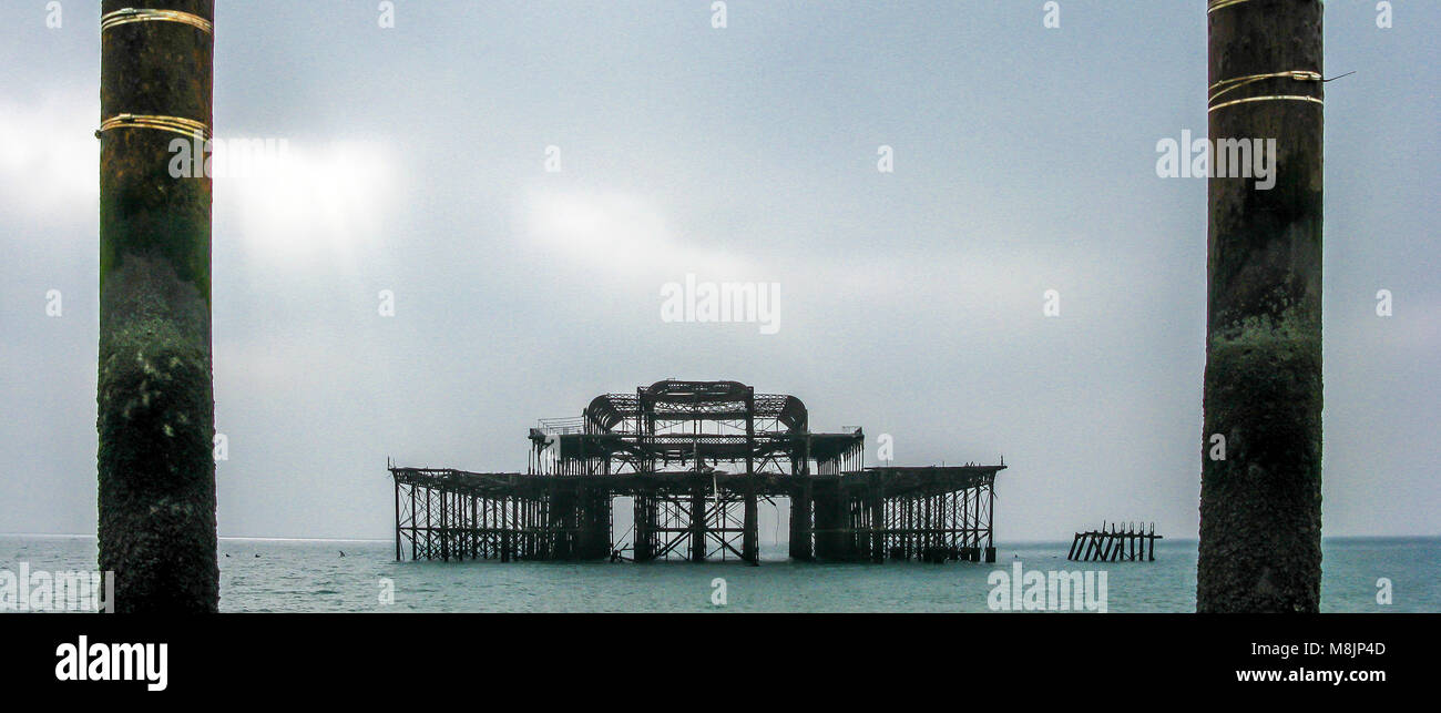 Skeletal cast iron frame of the burnt out West Pier in Brighton ominously  still stands stoically after being left - Stock Image