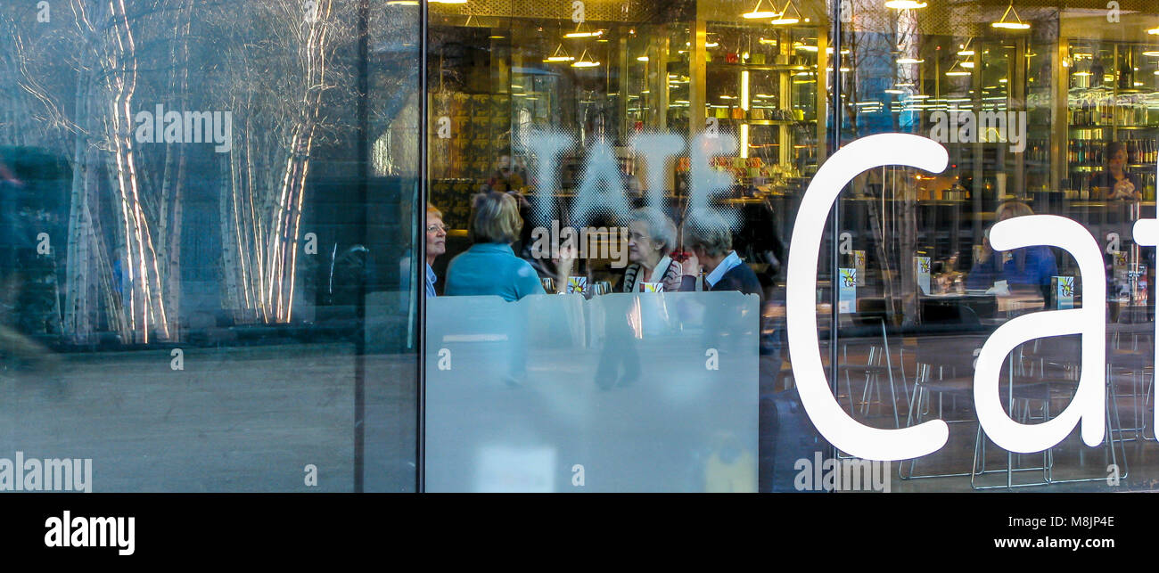 Reflections of trees in the Tate Modern's Cafe window as a group take their tea at the art gallery located in the Stock Photo