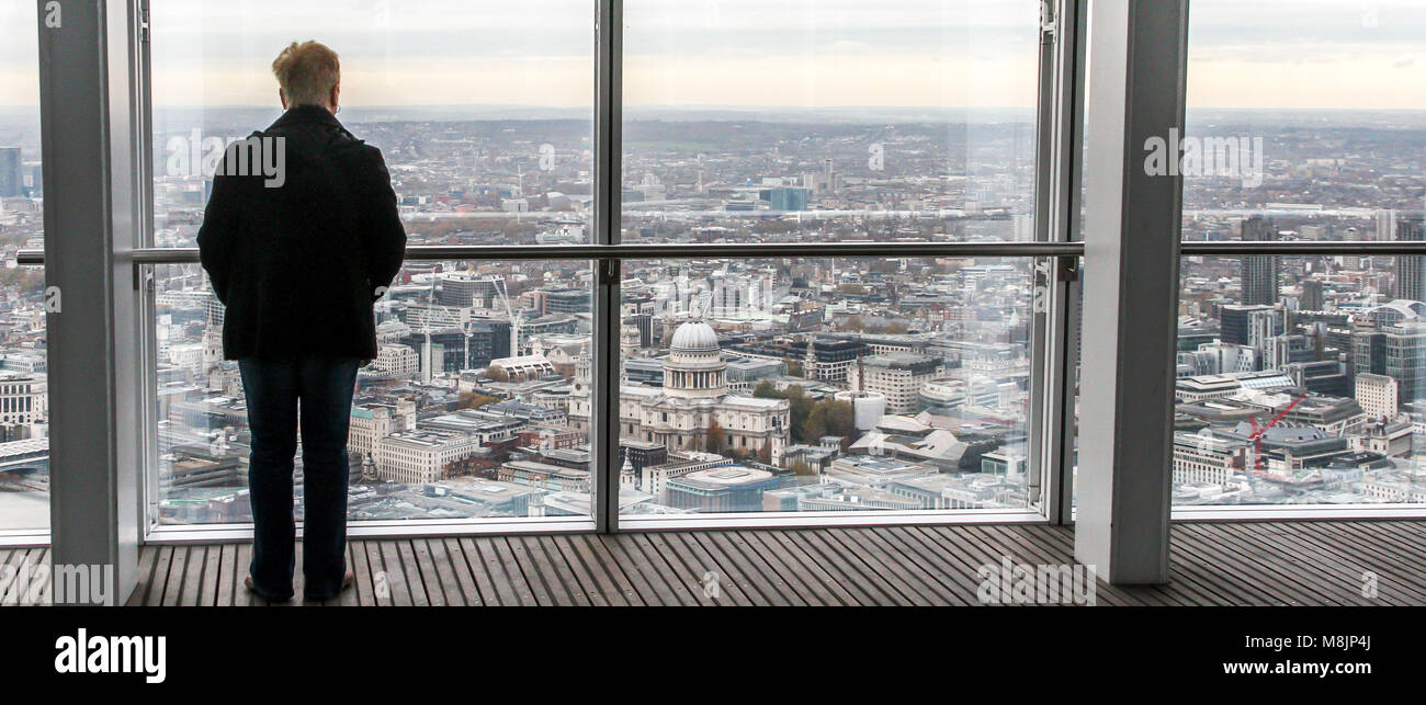 A solitary figure surveys the vertiginous view across London from the top of The Shard's viewing platform Stock Photo