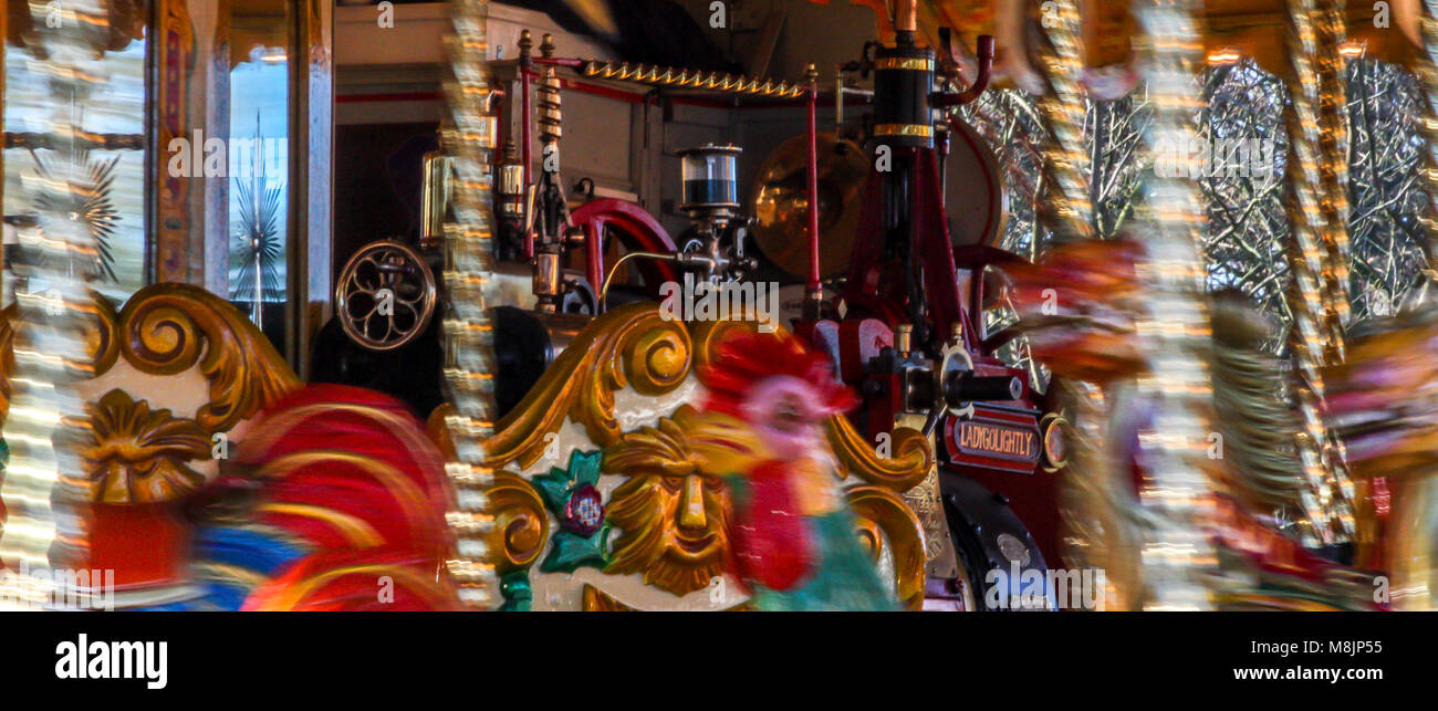 Traditional victorian steam powered colourful carousel fairground attraction fastly rotating at the fun filled funfare Stock Photo