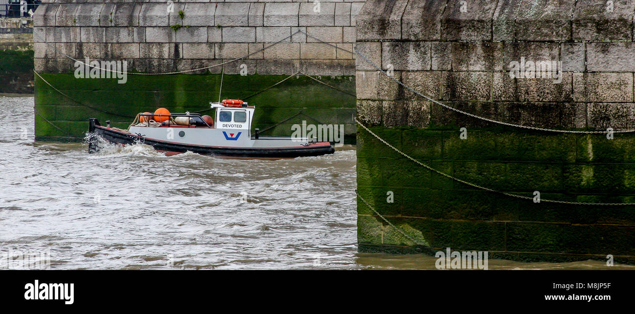 Tower Bridge's massive chained cutwaters with working tug boat Devoted passing between them in choppy Thames - Stock Image