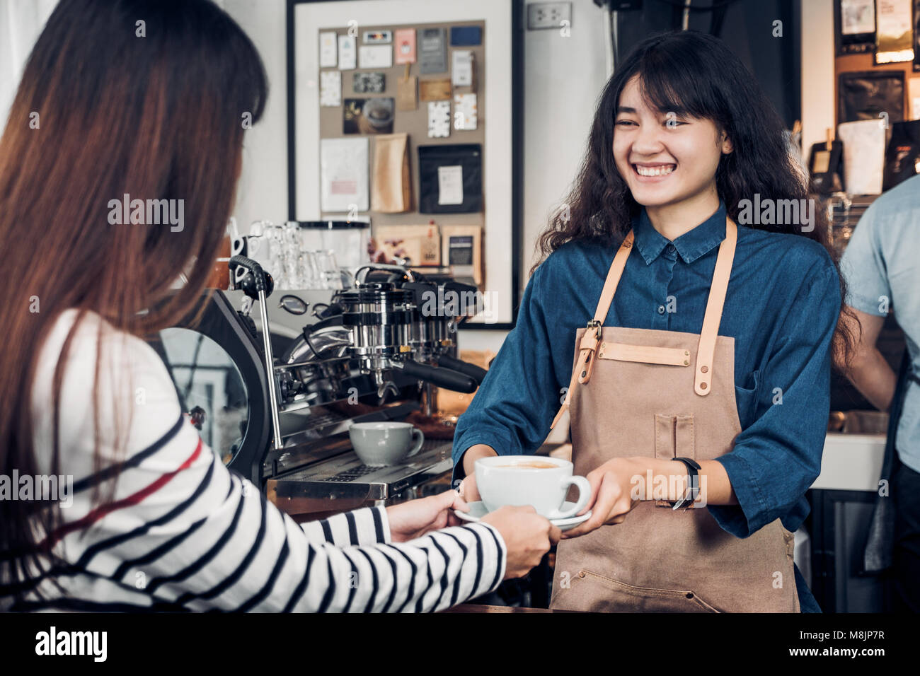 Asian woman barista wear jean apron holding coffee cup served to customer at bar counter with smile emotion,Cafe - Stock Image