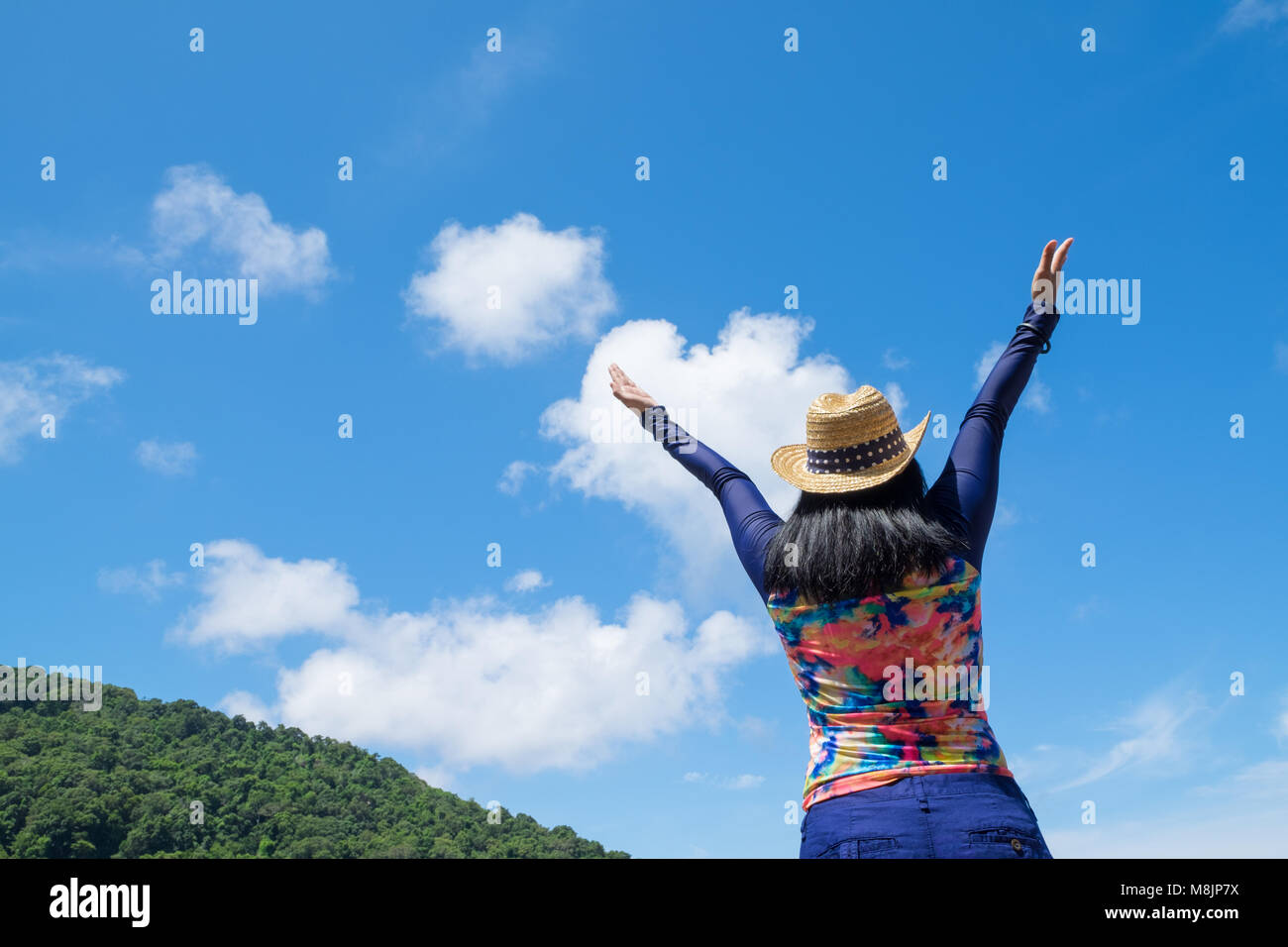 Traveller woman with colorful swimming suit raised arms to sky at top of mountain with happiness moment,Summer vacation - Stock Image