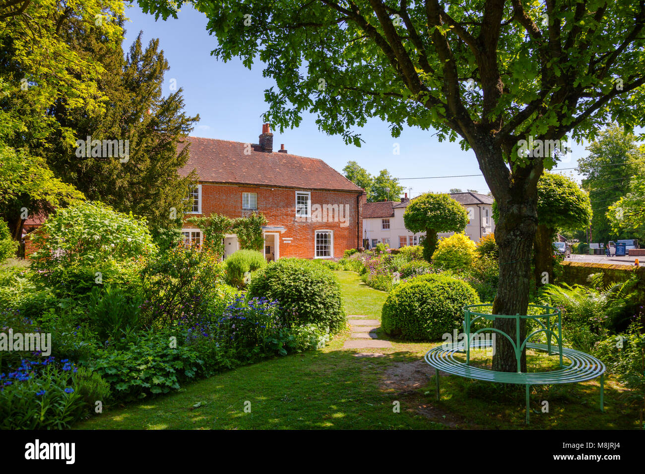 CHAWTON, UK - JUN 8, 2013: Round bench at formal garden of Chawton Cottage, an independent museum of novelist Jane - Stock Image