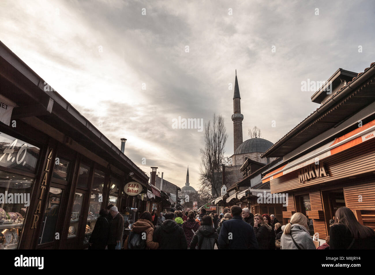 SARAJEVO, BOSNIA AND HERZEGOVINA - FEBRUARY 17, 2018: Street crowded with tourists and a Mosque Minaret in the Bascarsija - Stock Image