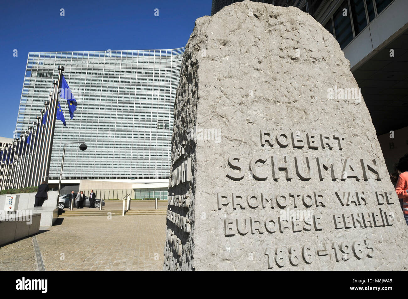 Robert Schuman monument and EU flags in front of Berlaymont building, headquarters of the European Commission, on - Stock Image