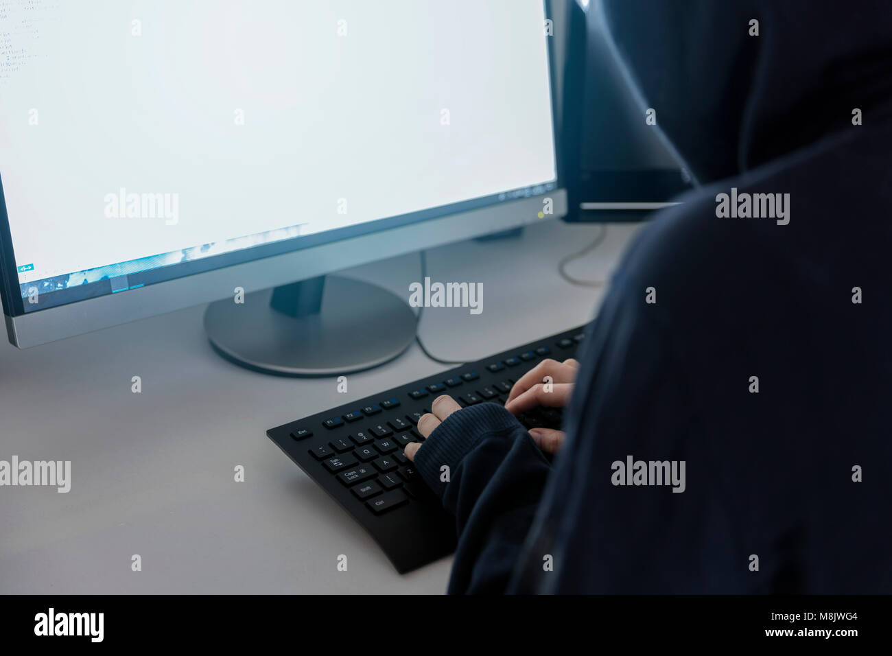 anonymous hacker in the hoodie, breaks the access to steal information and infect computers and systems. the concept - Stock Image