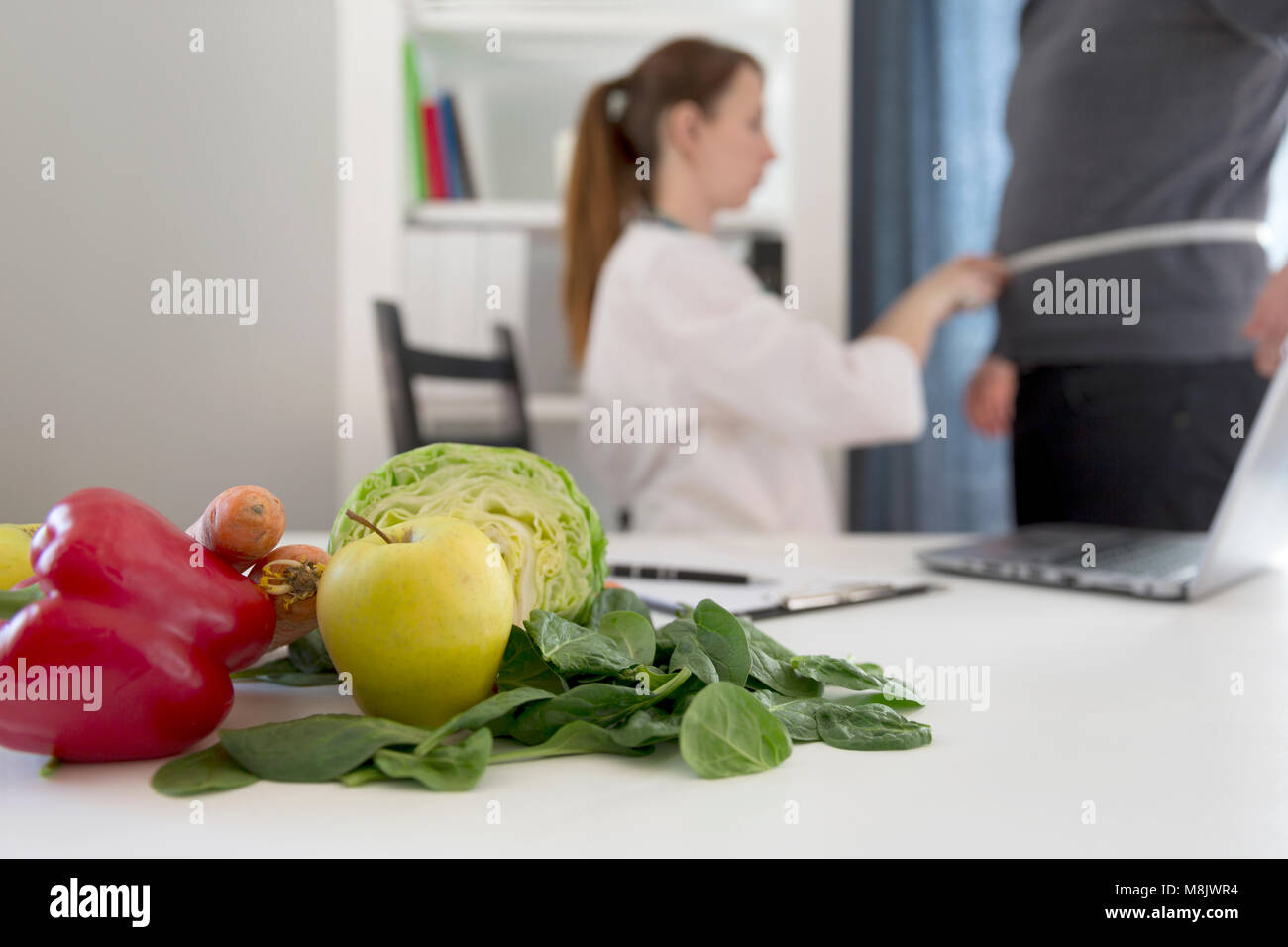 Vegetable diet nutrition and medication concept. Nutritionist measures patient's waist and offers healthy vegetables - Stock Image