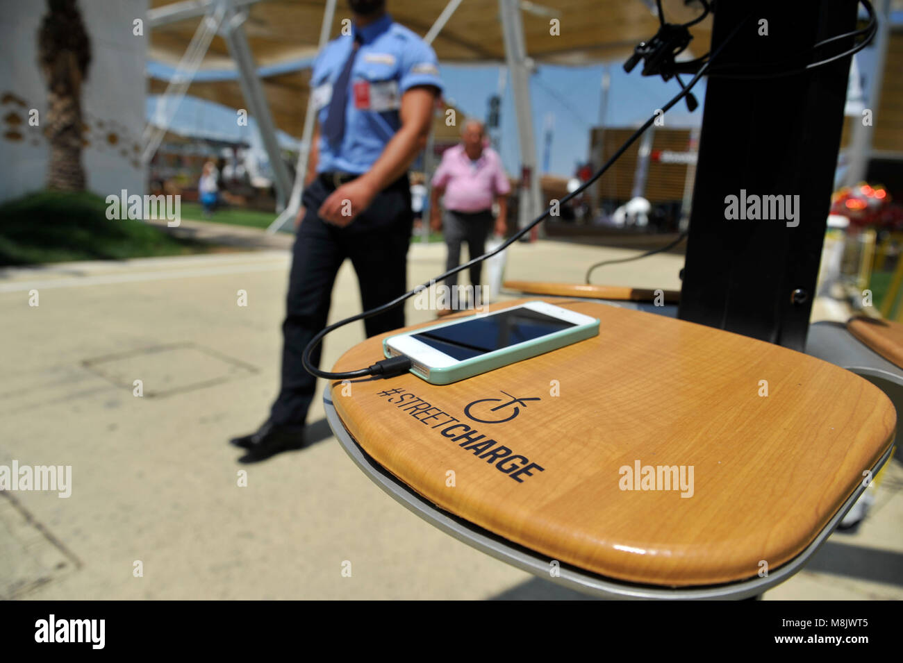Street charge for smartphone. Policeman on background. The photo was taken in Milan, Italy. - Stock Image