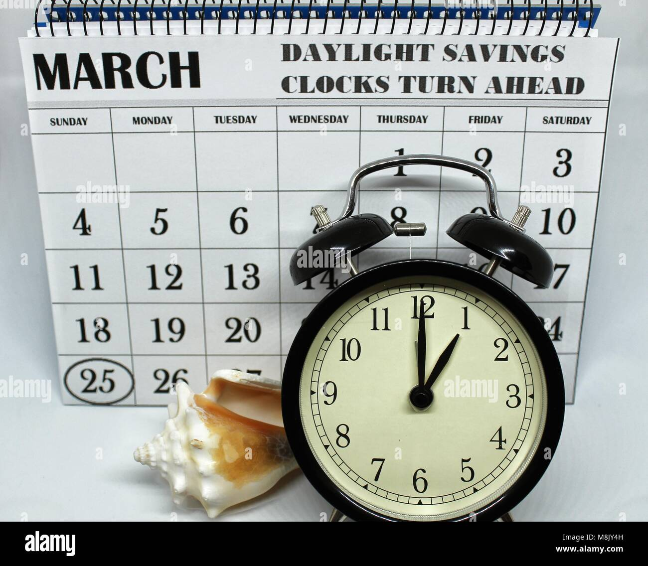 Daylight Savings Spring Forward sunday at 1:00 a.m. March 25 date indicated in the calendar. Clock next to a conch. - Stock Image