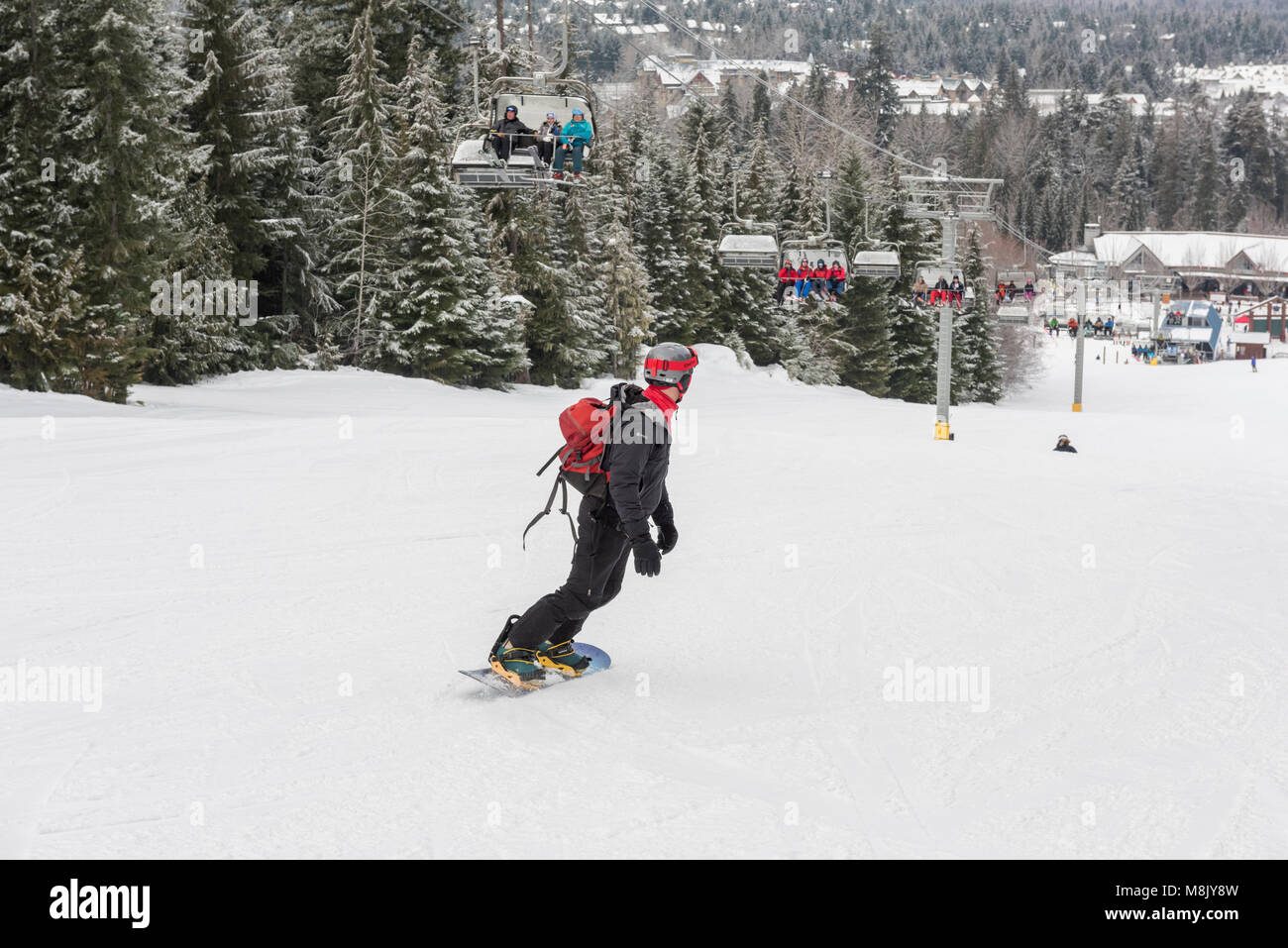Snowboarder heading down the run at  Whistler Blackcomb ski resort, British Columbia. - Stock Image