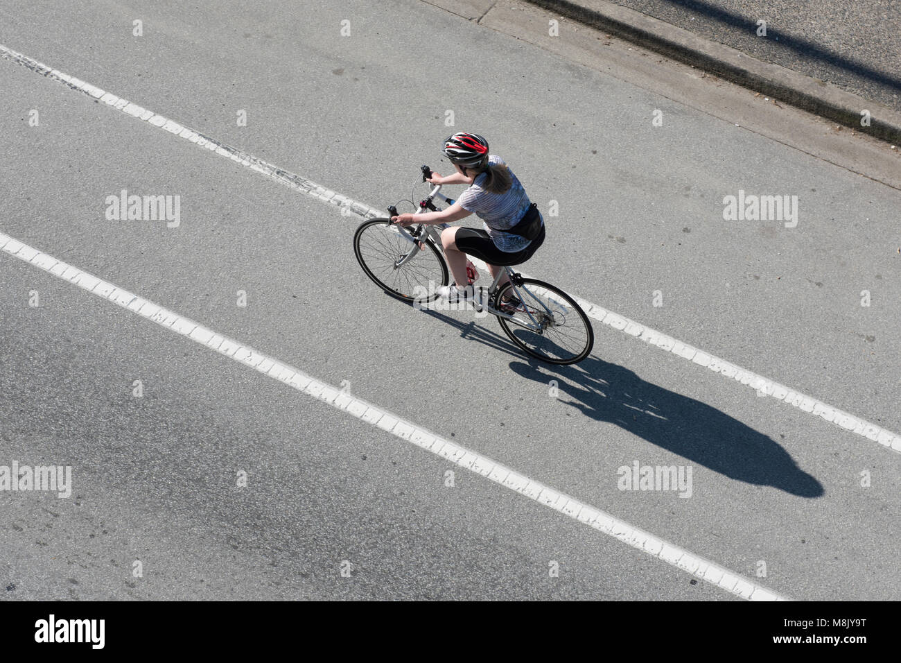 Bicyclist as seen from above traveling on the street via a bike lane, Vancouver City. - Stock Image