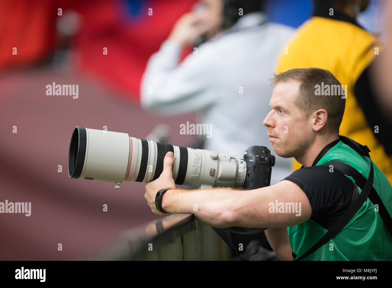 Professional sport photographer at an event. - Stock Image