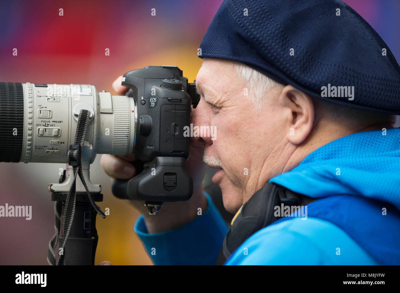 Professional Photographer looking through the viewfinder of his camera. - Stock Image