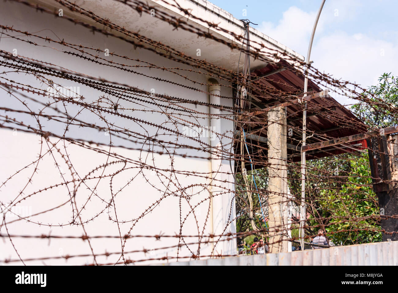 Barbed wire, razor wire and electricified fence around the perimeter of the Tuol Sleng Genocide Museum, Phnom Penh, - Stock Image