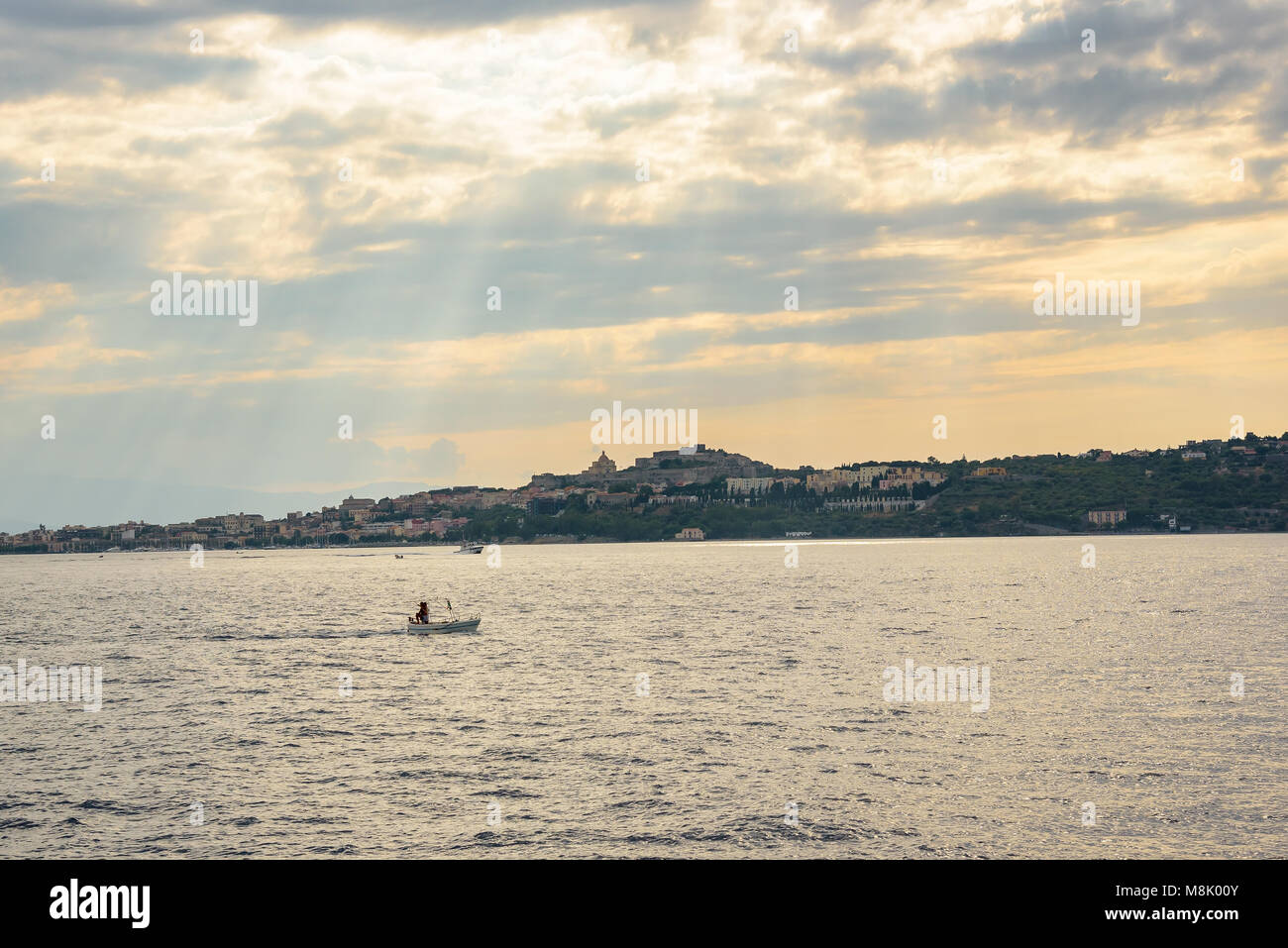 View of Milazzo town from the sea at sunset, Sicily, Italy Stock Photo