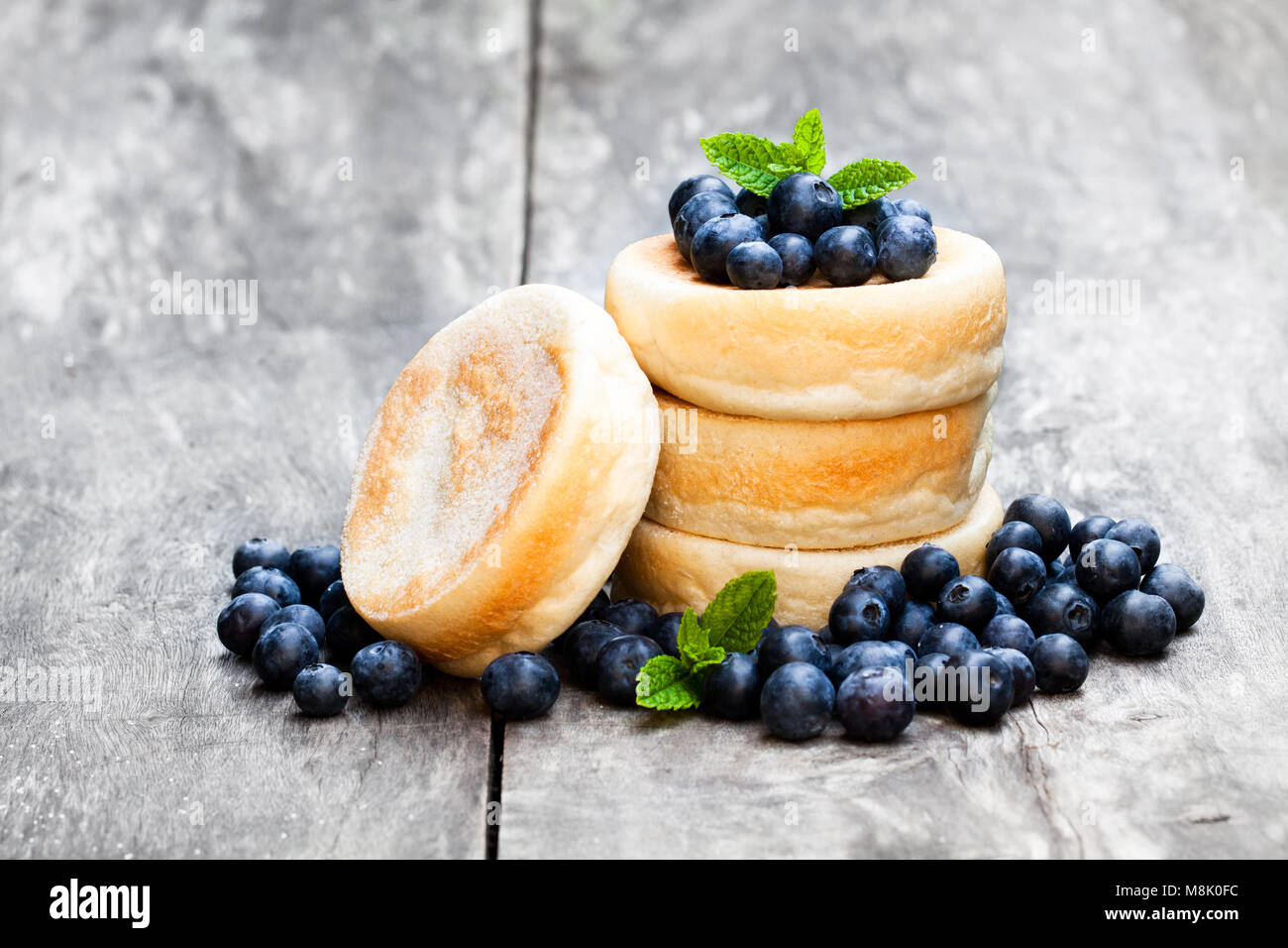 Stack  of thick yeast pancakes with blueberries on wooden table - Stock Image