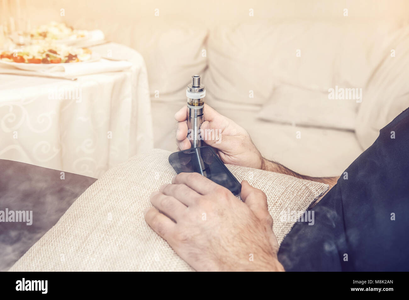 Electronic cigarette in the hands of a man who sits in a chair with a mobile phone. Copy space. Close up. - Stock Image
