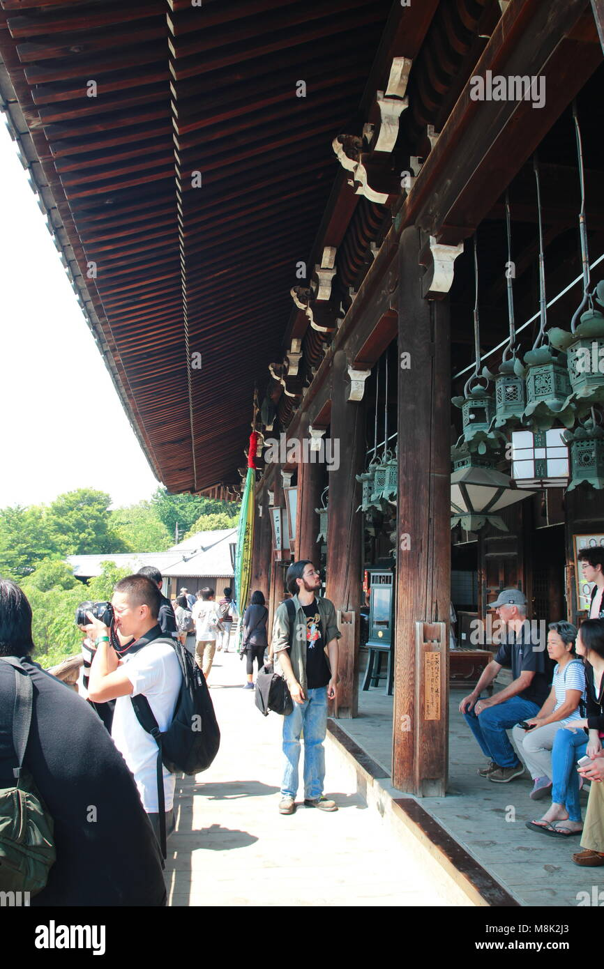 Foreigner tourists pay a visit and sightseeing at the the balcony, deck at Nigatsu-do Hall above the Todaiji temple - Stock Image