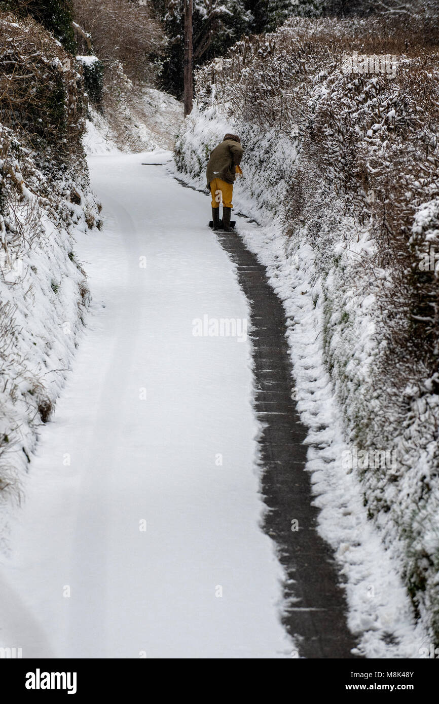 18.03.18. A man clears a lane in the village of Batheaston just outside Bath in Somerset after heavy snowfall overnight. Stock Photo