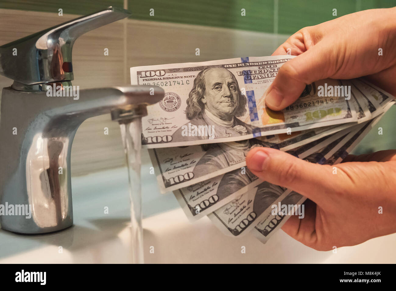 Money Launder. US dollars hung under running tap water as a metaphor for money laundering. black, market - Stock Image