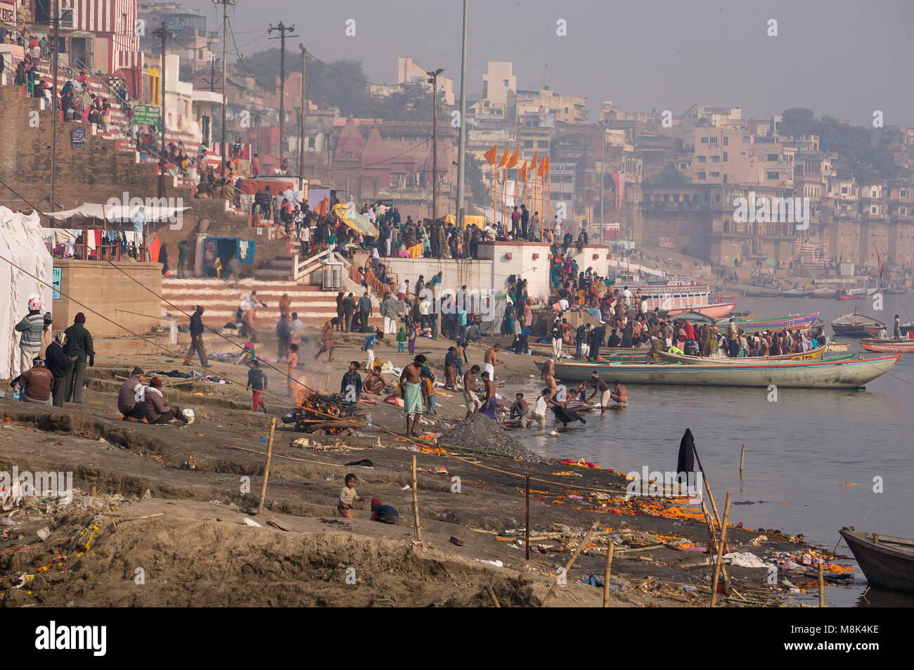 VARANASI, INDIA. February 28, 2017: A typical day on the banks of the river Ganges: Hindus burn dead bodies, washed - Stock Image