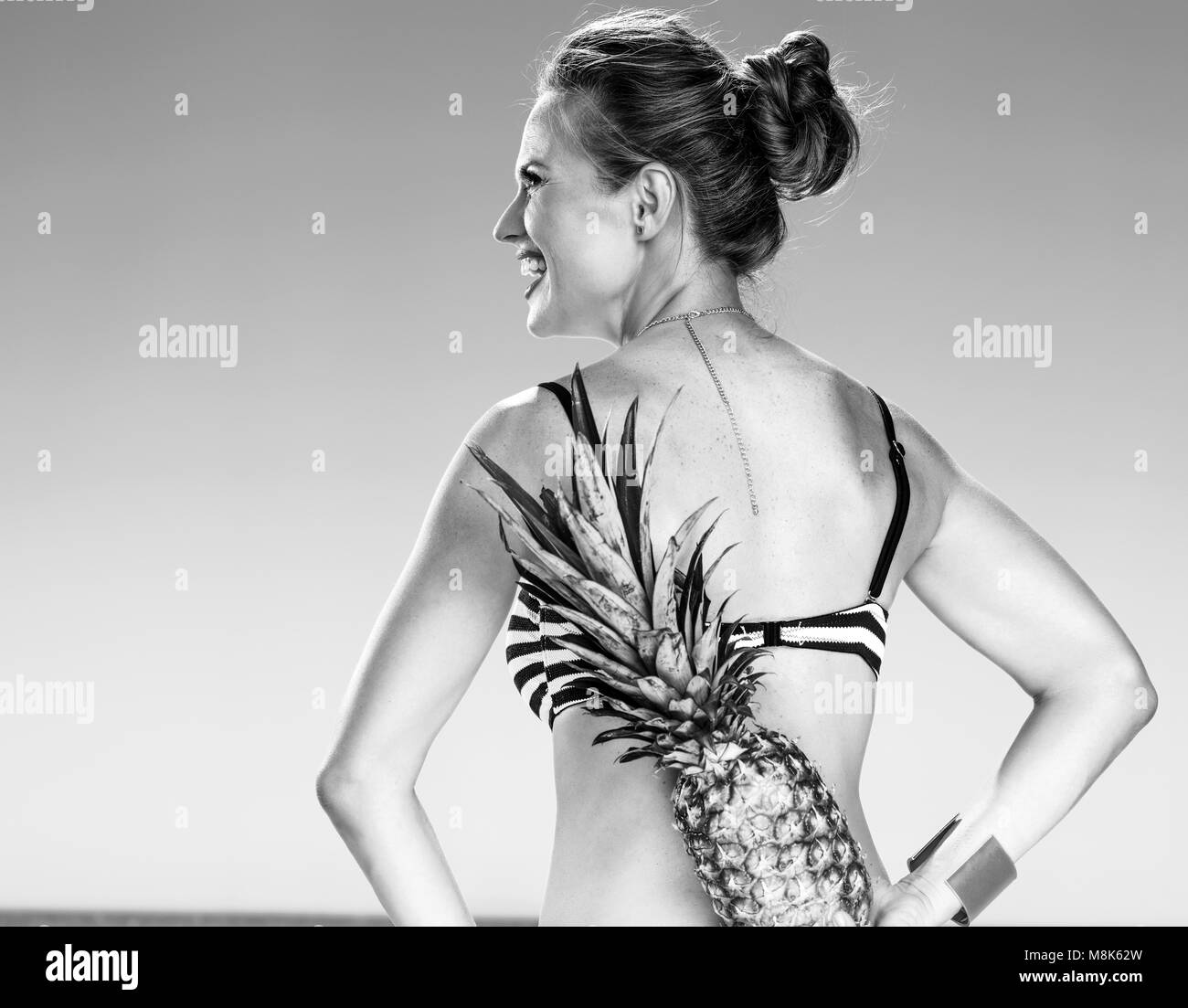 Perfect summer. Seen from behind young woman in bikini on the seacoast with pineapple - Stock Image