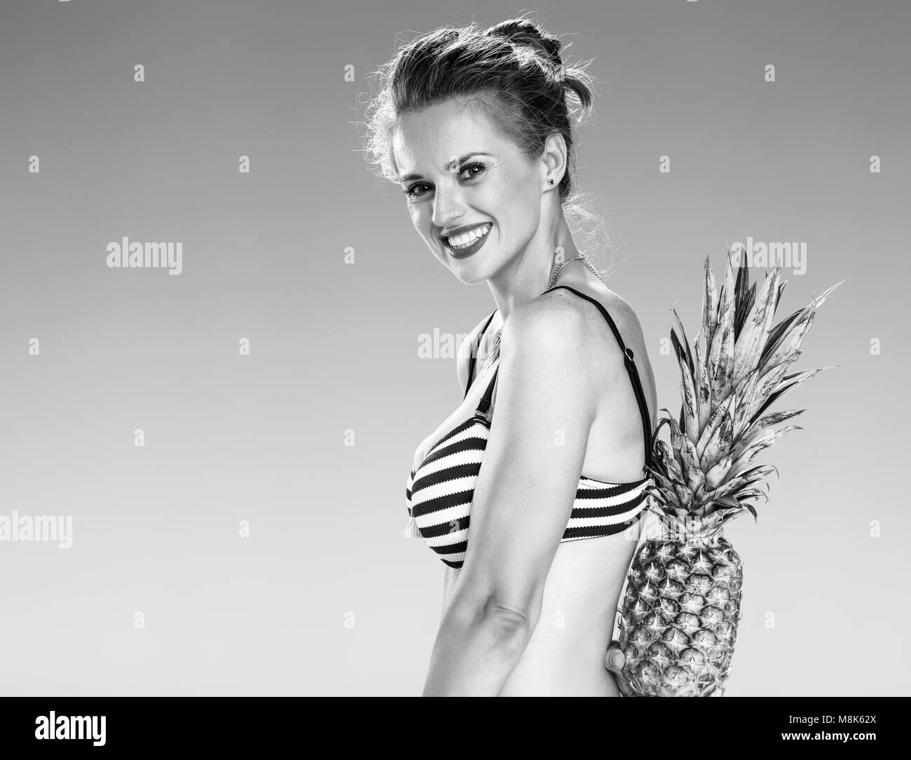 Perfect summer. smiling young woman in bikini on the seacoast hiding pineapple behind back - Stock Image