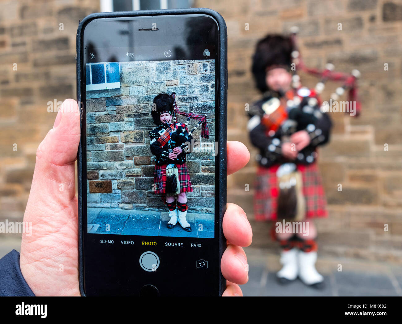 Tourist taking photo of Scottish man in tartan playing bagpipes on the Royal Mile in Edinburgh Old Town, Scotland, - Stock Image