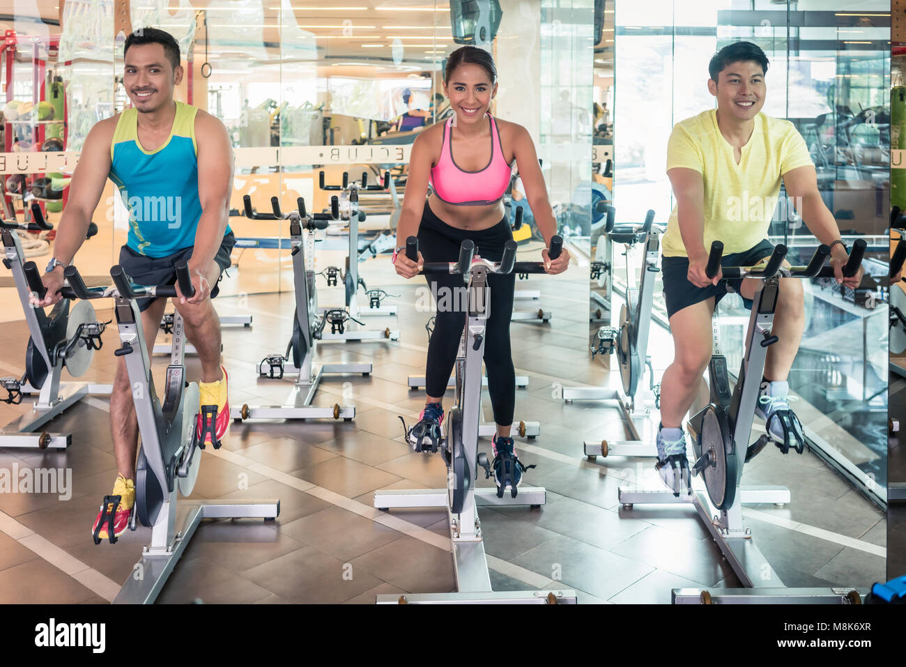 Handsome and confident young man during group class of HIIT indoor cycling - Stock Image