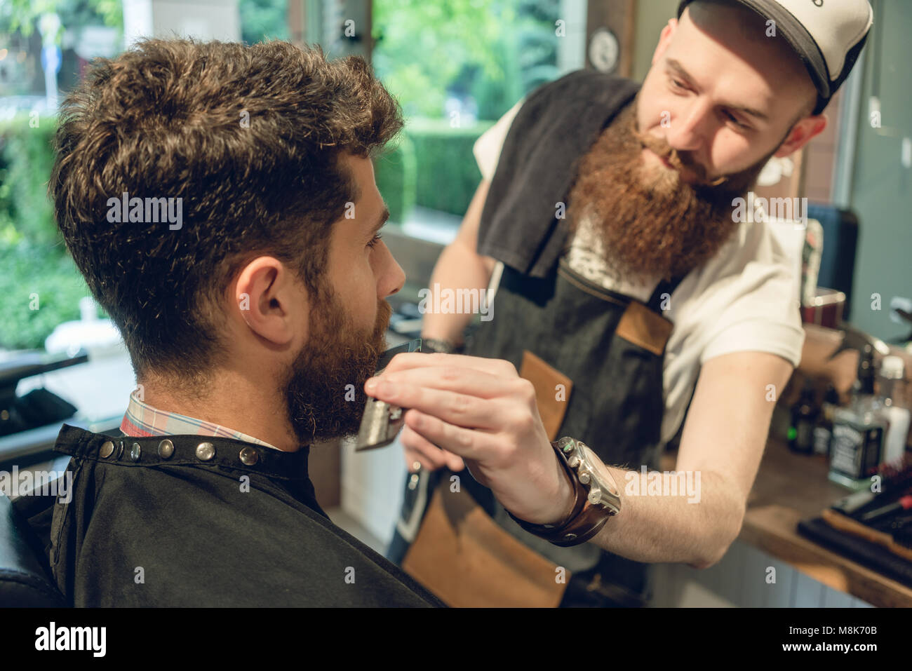 Handsome young man sitting on the chair of a barbershop - Stock Image