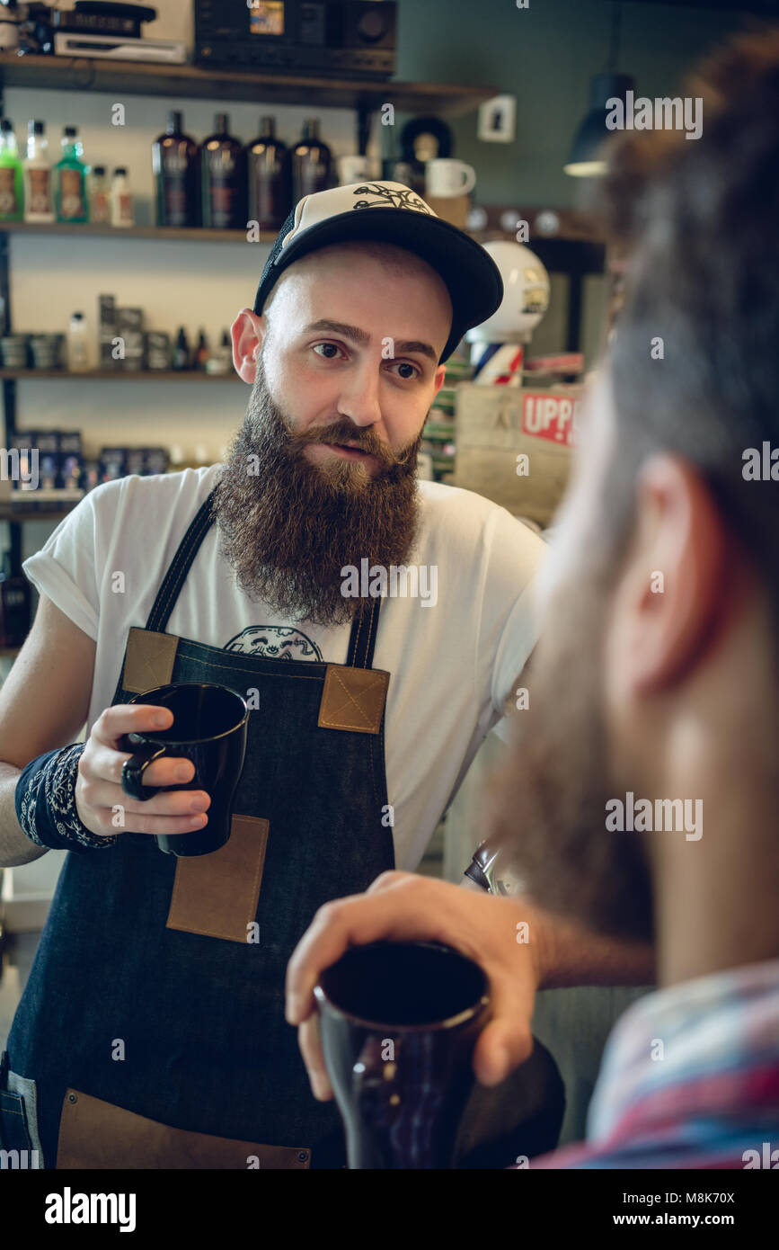 Dedicated hairstylist drinking coffee with his customer and friend - Stock Image