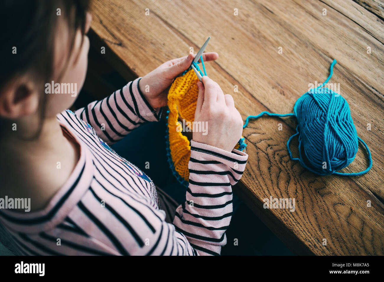 Young girl knitting a circle scarf with yellow and blue coloured yarn. Sitting at the wooden table, close up over - Stock Image