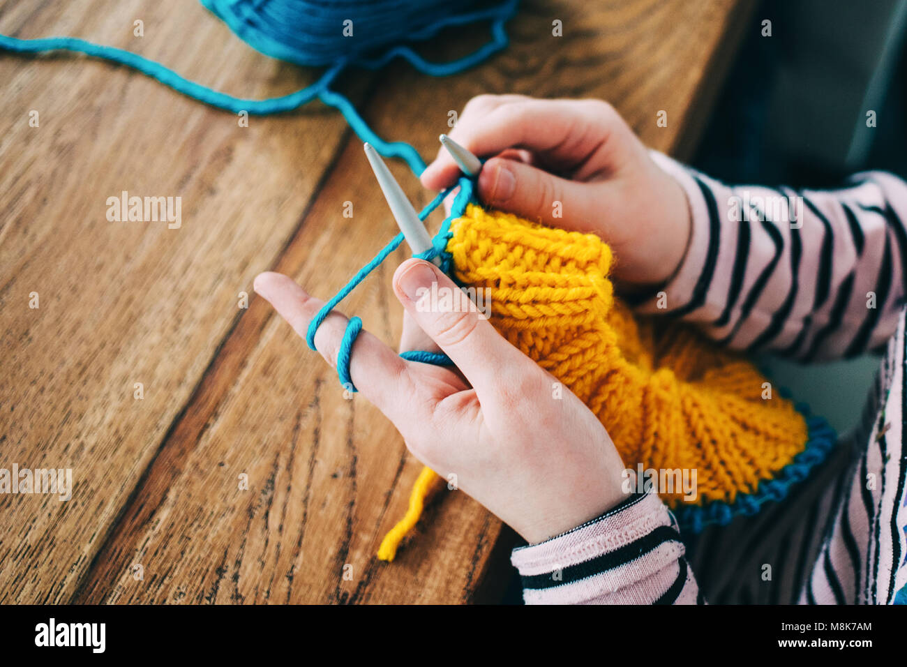 Young girl knitting a circle scarf with yellow and blue coloured yarn. Sitting at the wooden table, close up of - Stock Image