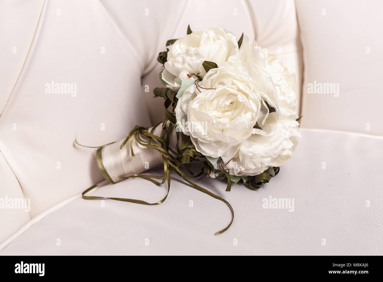 Bridal bouquet of white rose in bright colors on white leather chair ...
