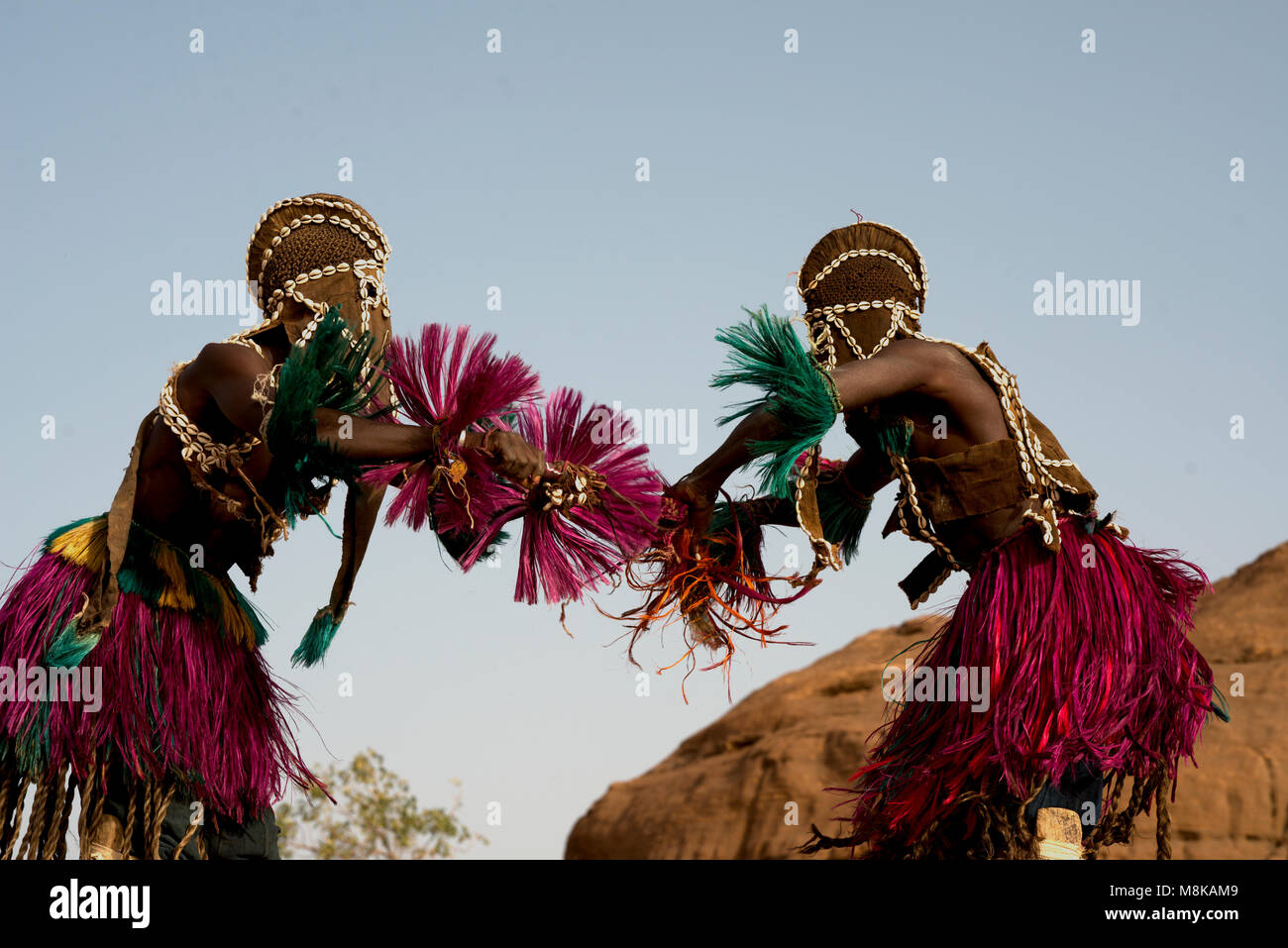 Two masked indigenous Dogon men in traditional costumes taking part in a traditional dance. Mali, West Africa. - Stock Image