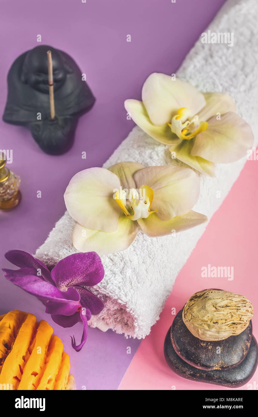 Beautiful orange handmade soap and towel with Orchid flowers for Spa treatments on two-tone background. Incense - Stock Image