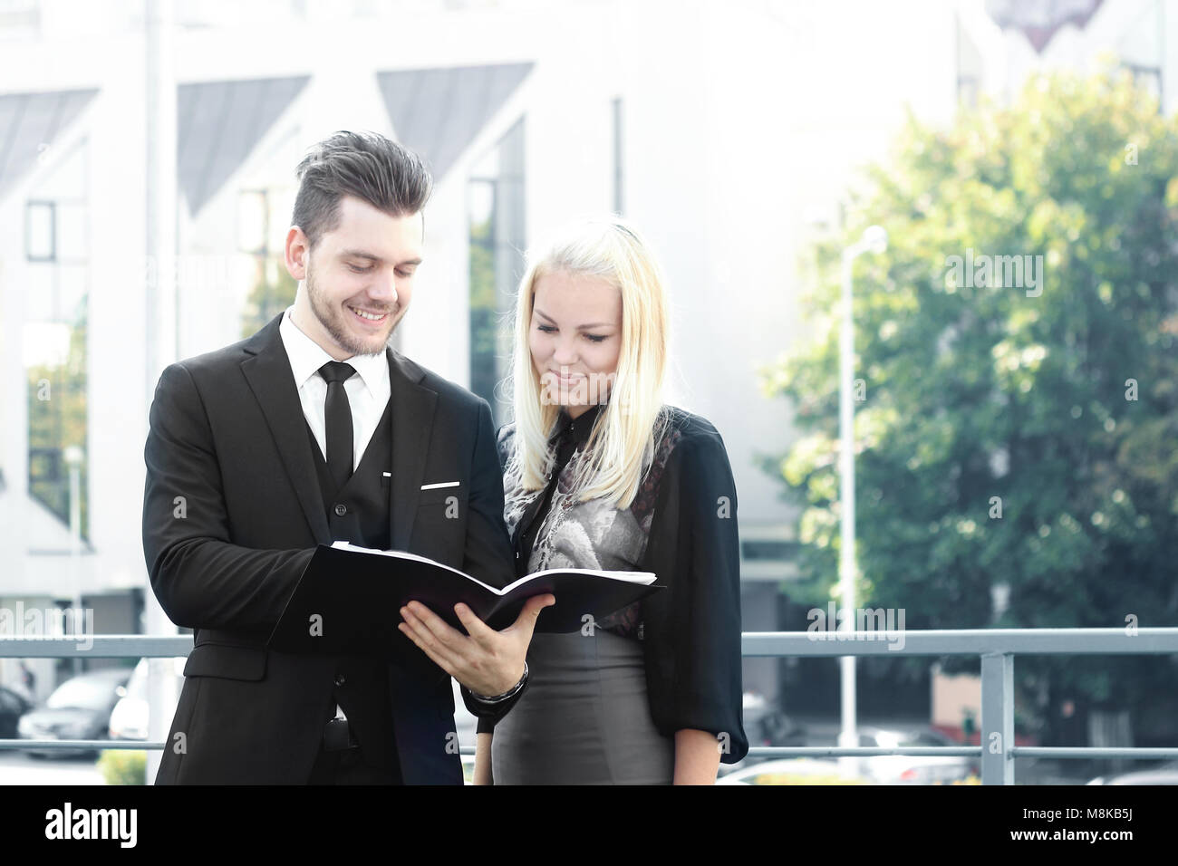 couple of employees reading documents standing near the office - Stock Image
