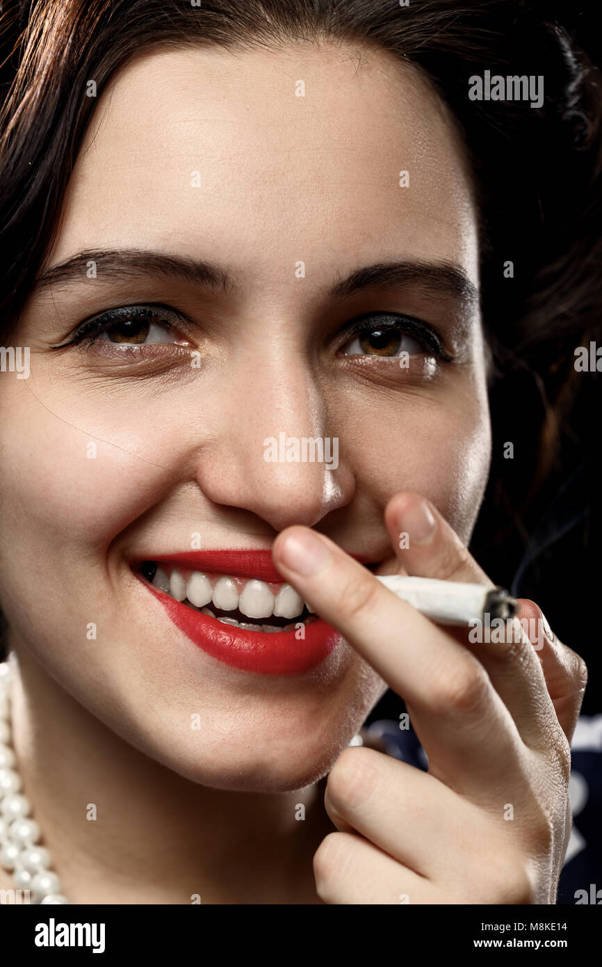 blond young woman smoking joint on black background - Stock Image
