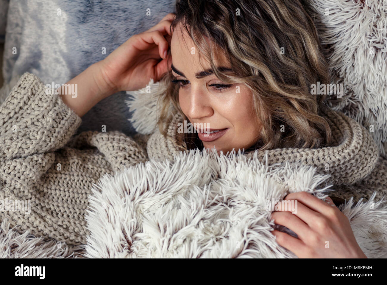 portrait of beautiful woman relaxing in bedroom at home - Stock Image