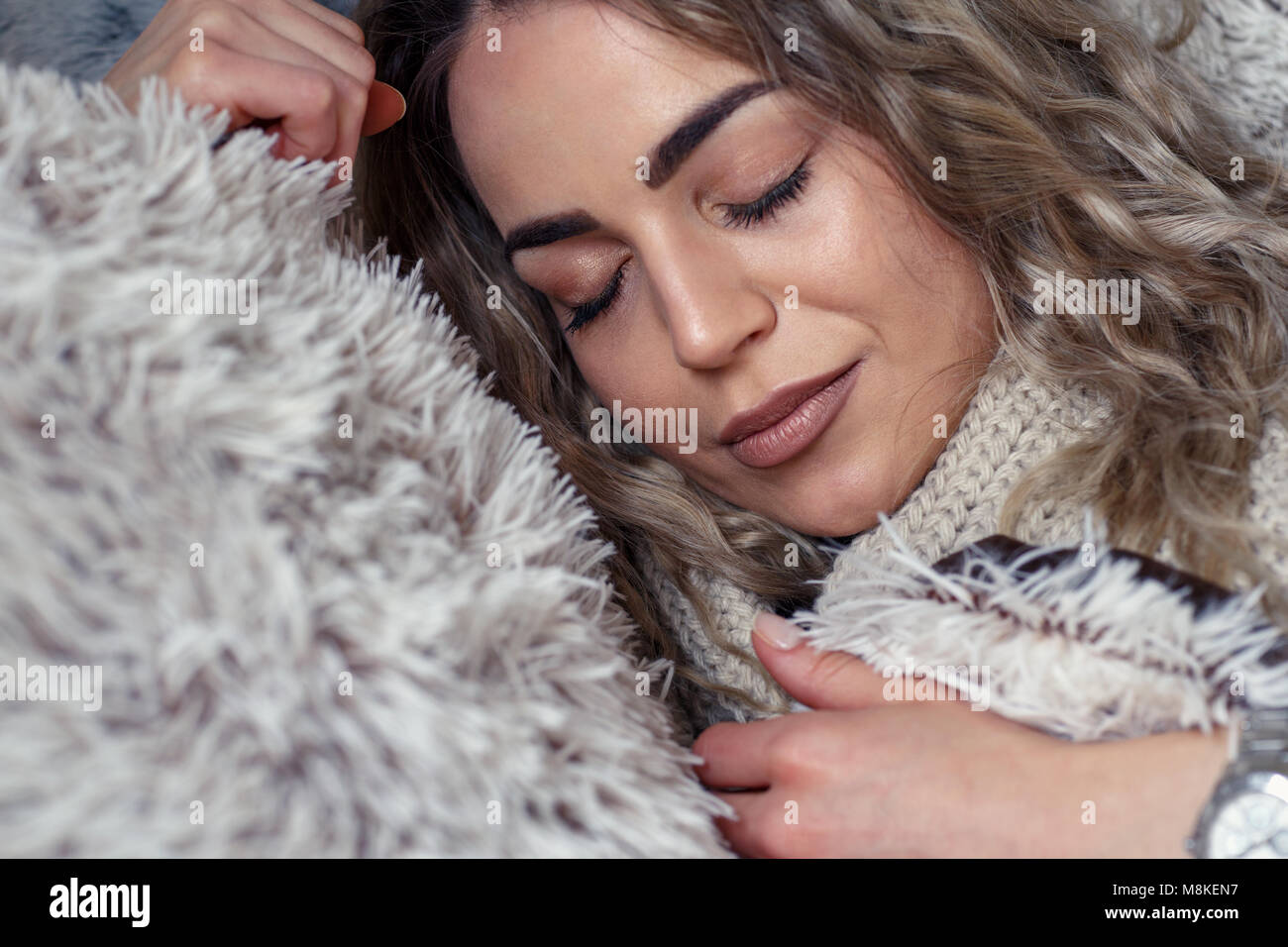 Beautiful young woman sleeping in a comfortable bed at home - Stock Image