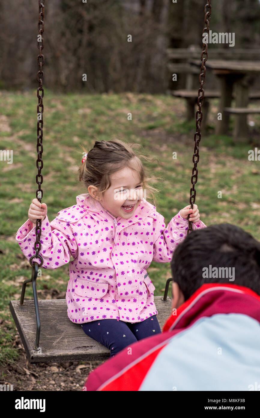 Child, Playing, Playground – smiling cute girl swinging - Stock Image