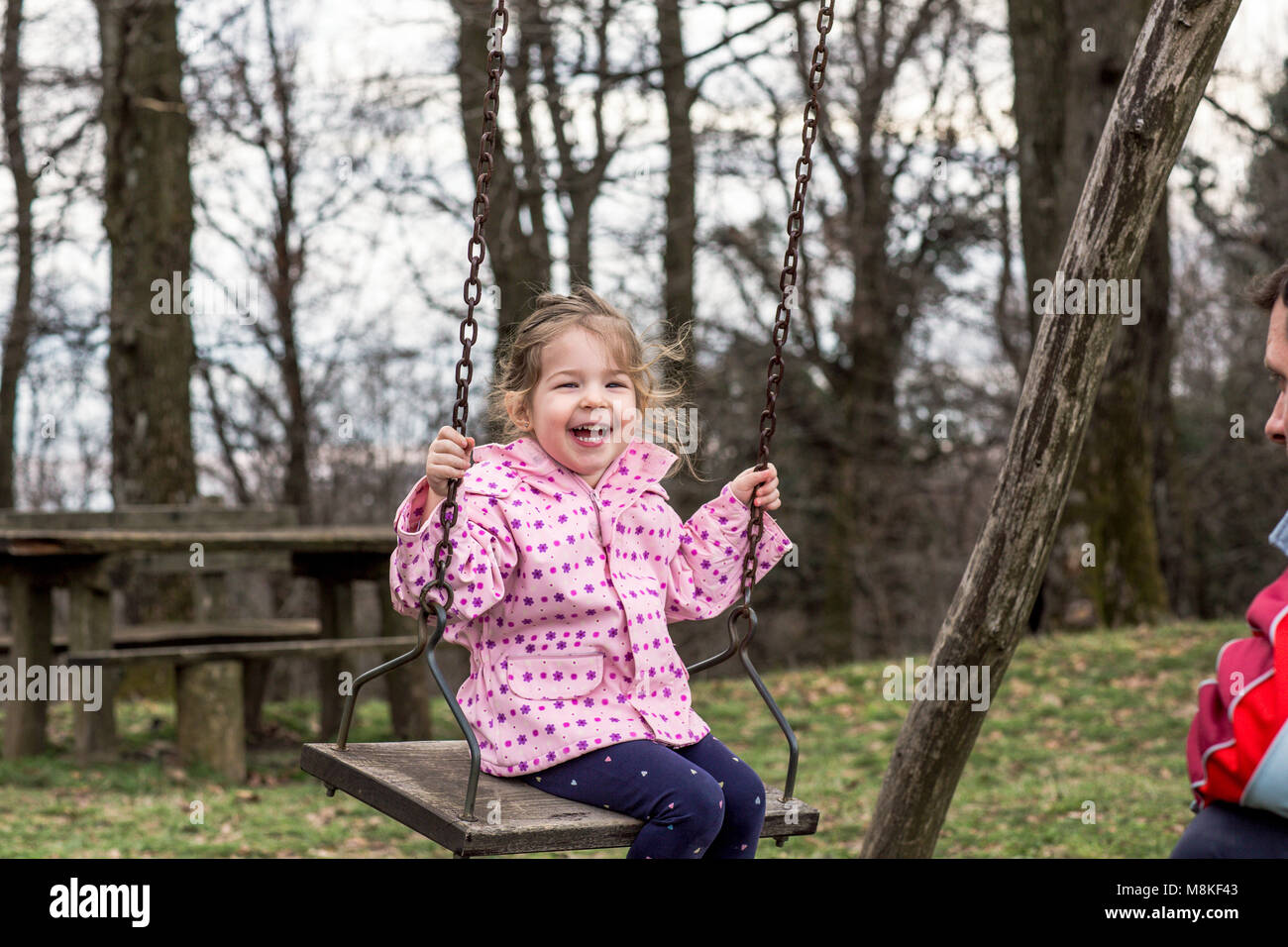 smiling cute girl swinging with her father - Stock Image