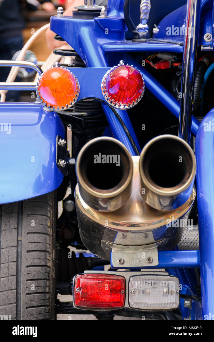 back side of a blue motorcycle. lovely detail shot of lights and shiny exhaust pipes - Stock Image