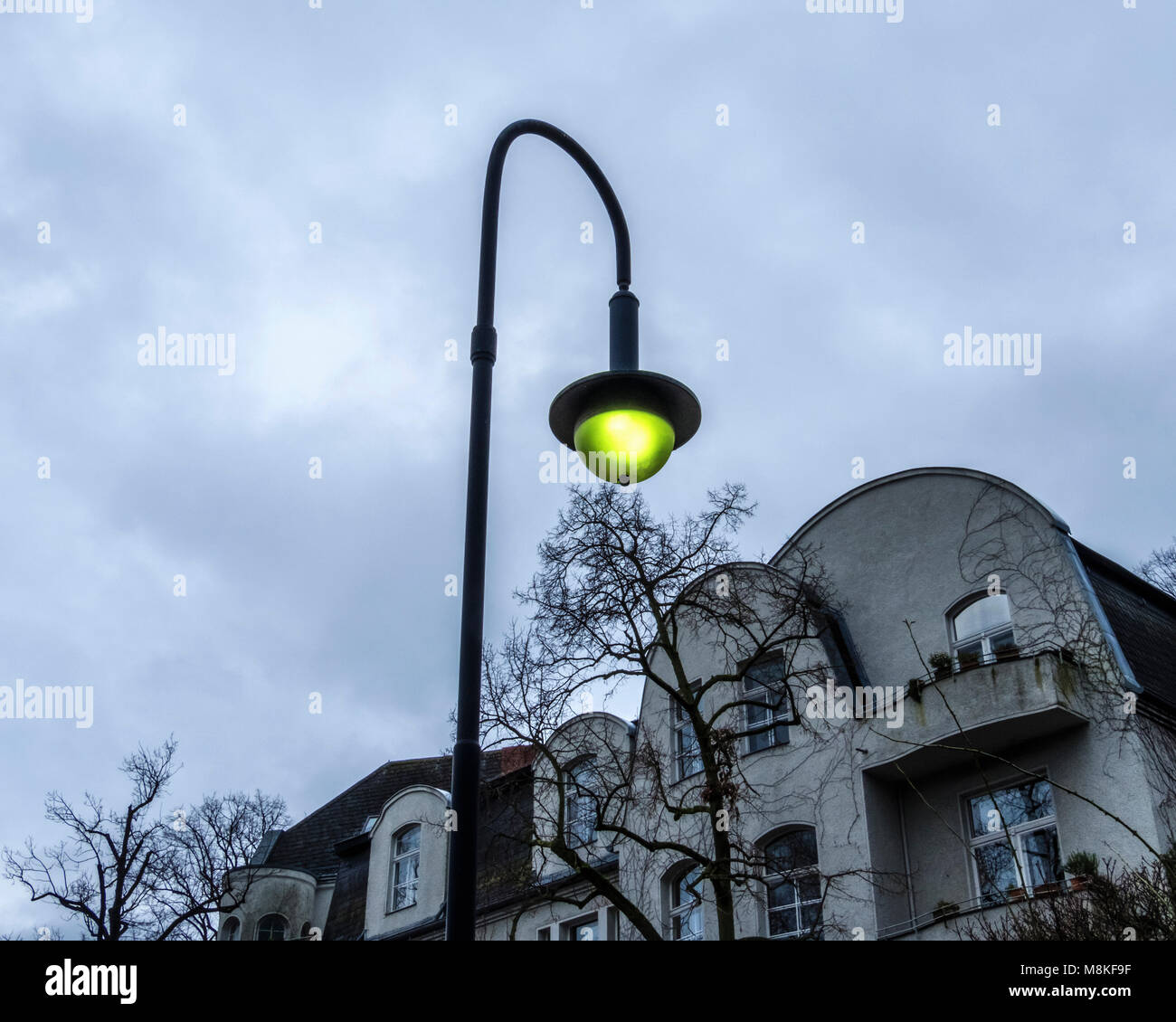 Berlin,Grunewald,Old street lighting, lamp post with yellow light in front of apartment building in suburbia - Stock Image