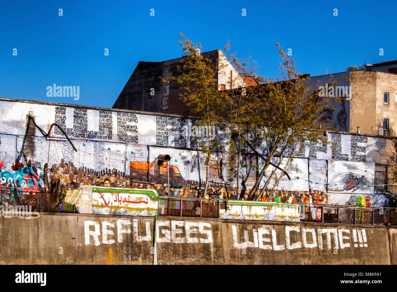 Berlin Friedrichshain.Refugees welcome sign and atrwork showing boat loaded with people next to Spree river, - Stock Image