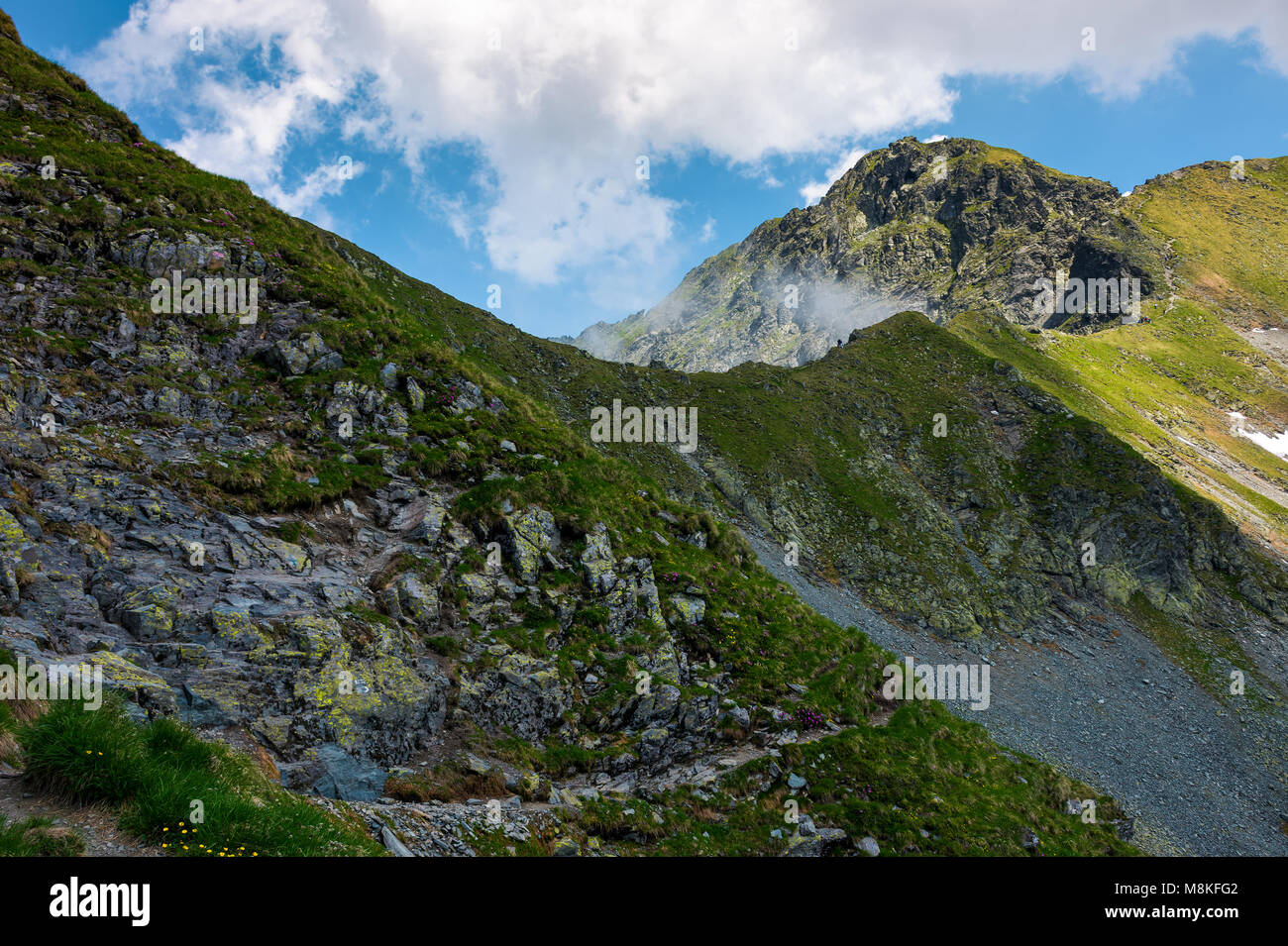 Peaks of mountain ridge among the clouds. Mighty formations with rocky tops and grassy hills. beautiful summer nature - Stock Image