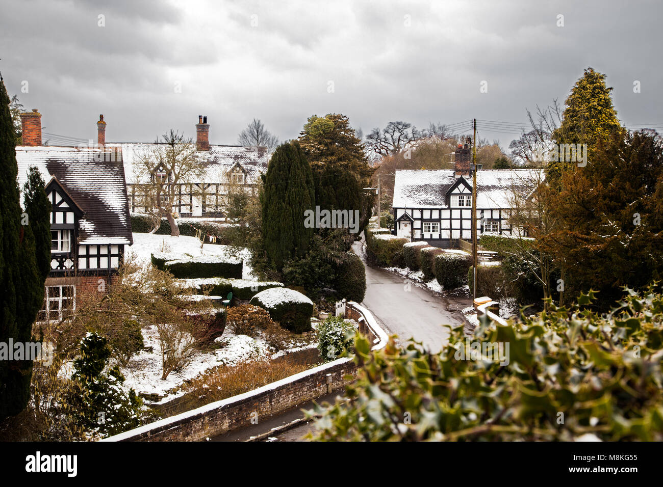 Snow covered black and white half timbered houses in the picturesque   Cheshire village of Barthomley  England UK - Stock Image
