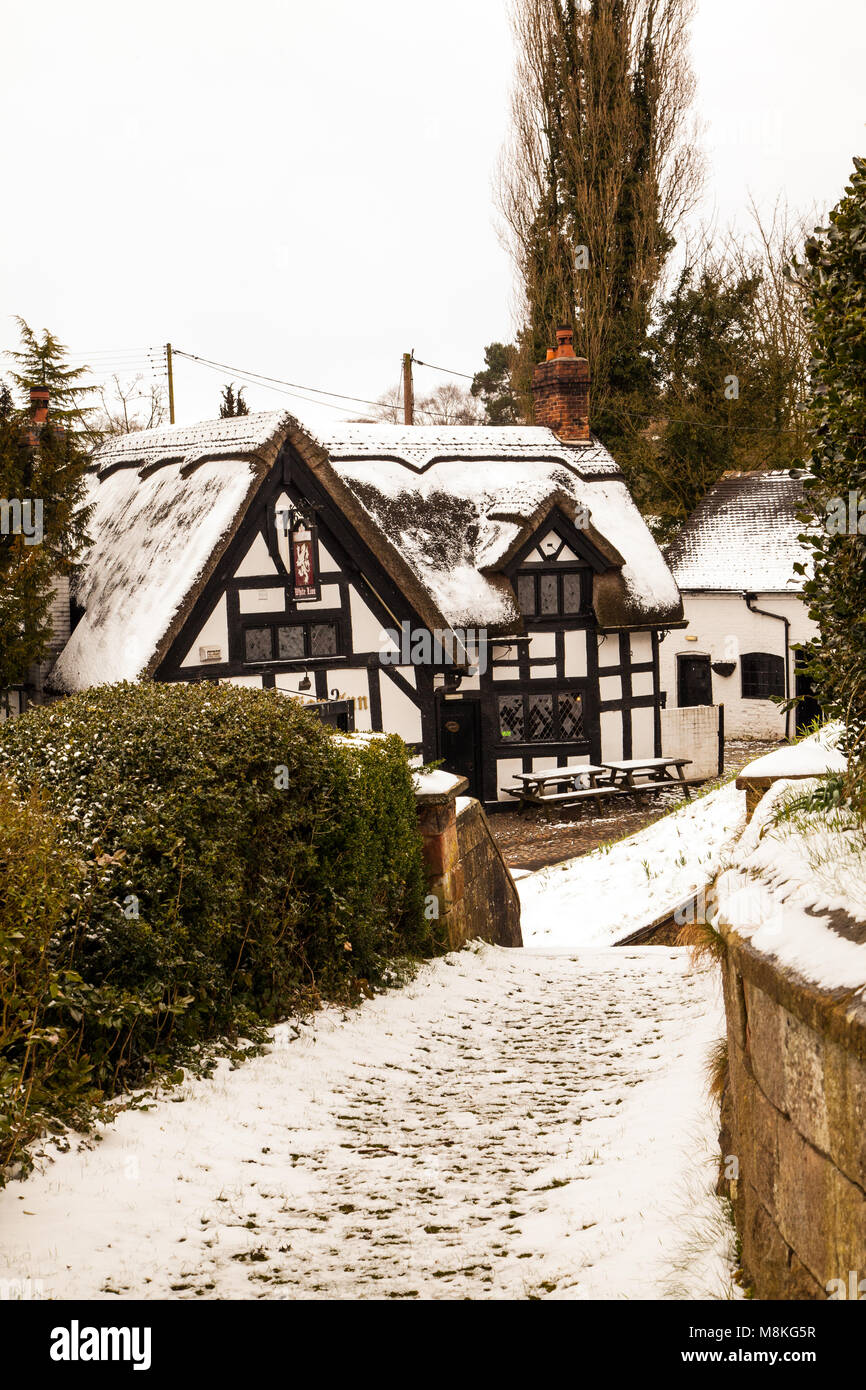 Snow covered black and white half timbered houses and the White Lion  inn in the picturesque  Cheshire village of - Stock Image